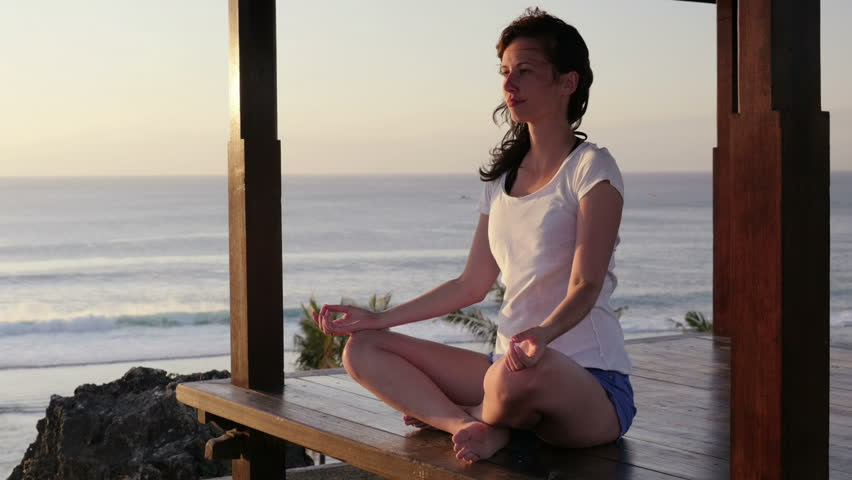 woman meditating in a lotos yoga pose looking at sunset