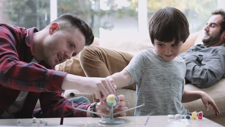 Same sex couple family playing and painting