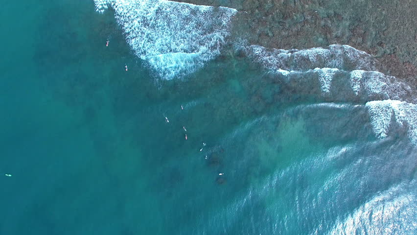 Aerial overhead shot top down view of waves coming in and push in to surfers in the ocean