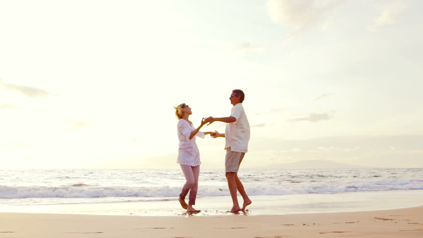 Sunset walk on the beach retirement older couple on for Tropical vacations for couples