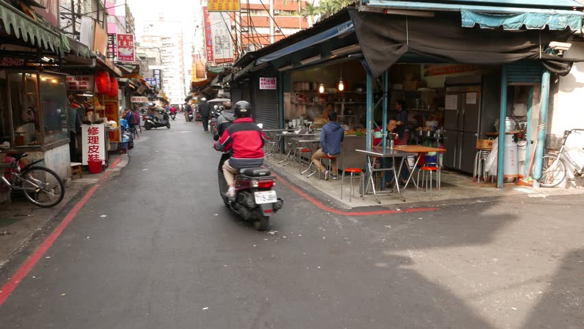 TAIPEI, TAIWAN - FEBRUARY 12, 2015: Typical quiet street at Wanhua District of Taipei city,  Street restaurant, small cheap eatery place, under canopy on right side, living house on left