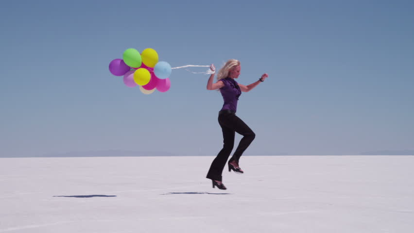 Cinemagraph - Woman skipping with balloons at salt flat. Looping Motion Photo.