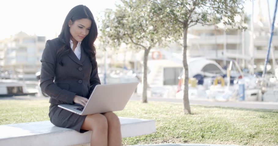 Business woman sitting and working on her laptop computer while relaxing on bench - 4K stock video clip