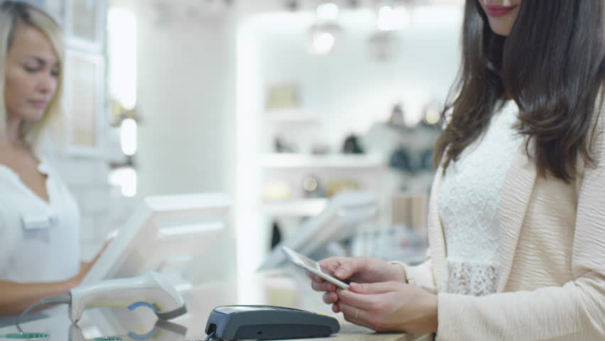 Young woman is paying with her smartphone application at the cash desk in a department store. Shot on RED Cinema Camera in 4K (UHD).