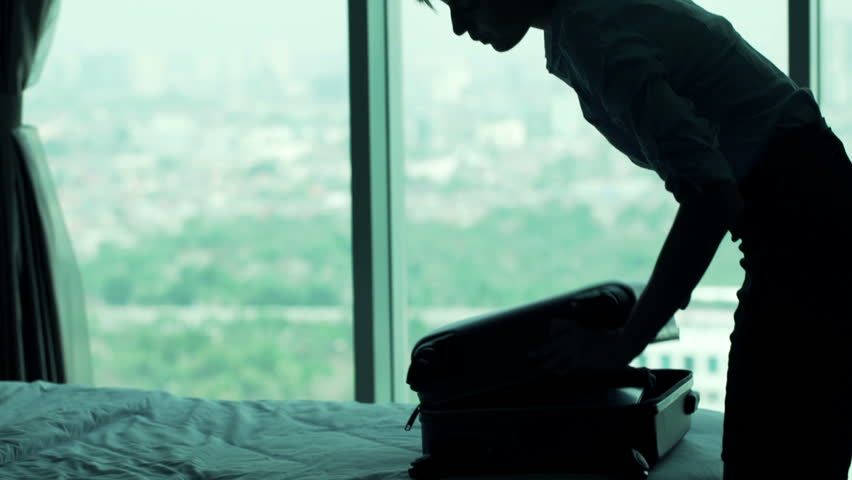 Young businesswoman packing suitcase in hotel room   | Shutterstock HD Video #13161653