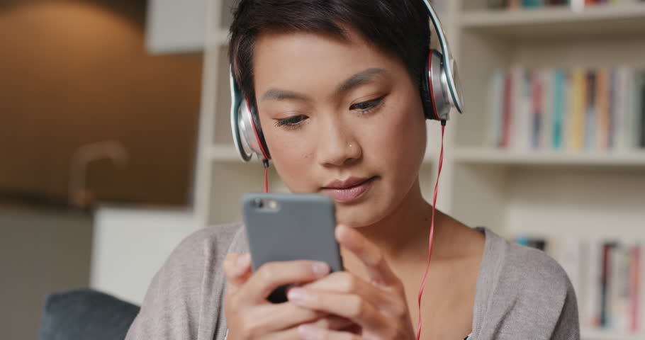 Beautiful Asian woman at home listening to music on smart phone technology with headphones   Shutterstock HD Video #13165307