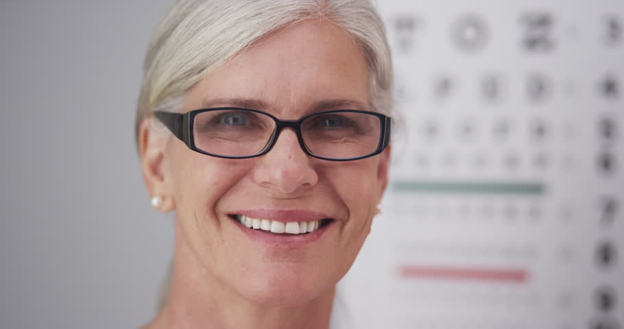 Beautiful mature woman wearing prescription eyeglasses - 4K stock video clip