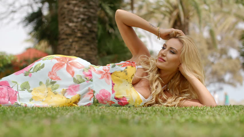 Blond Woman Wearing Floral Print Sun Dress Lying on Side with Head Propped on Elbow and Looking into the Distance in Tropical Location - HD stock video clip