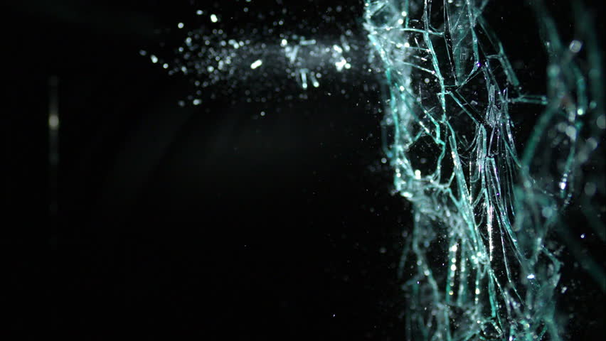 Plate glass window shattering on black from the side, isolated on black breaking in slow motion in 4k