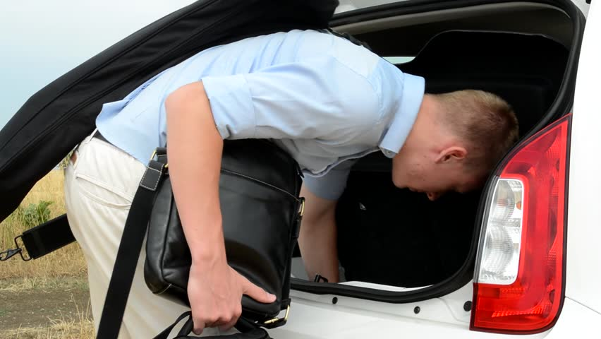 Young man putting bags inside the car trunk in the countryside   Shutterstock HD Video #13381253