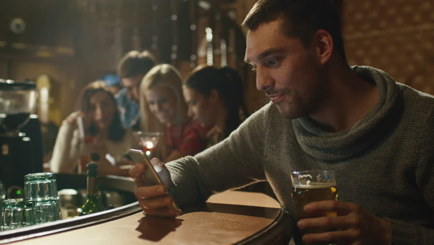 Happy man holds a glass of beer while using a smartphone in a bar. Shot on RED Cinema Camera in 4K (UHD).