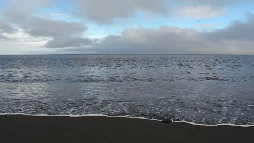 Waves roll towards shore, engulf sand, retreat, create a beautiful reflection of clouds and blue sky. 1080p