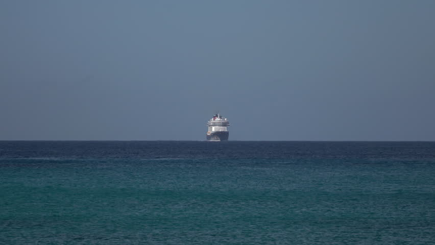 GRAND CAYMAN - NOV 2015: Grand Cayman cruise ship arrives distant Caribbean Sea. Tourism and off shore banking are main economic stimulus. Beach and resorts cater to tourists. Vacation destination.