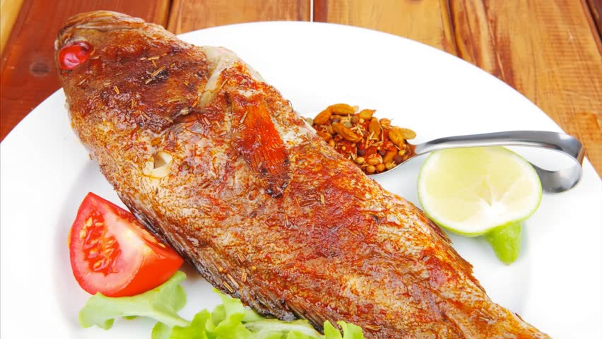 Main portion of two grilled fish served on plate with for Grilled fish seasoning