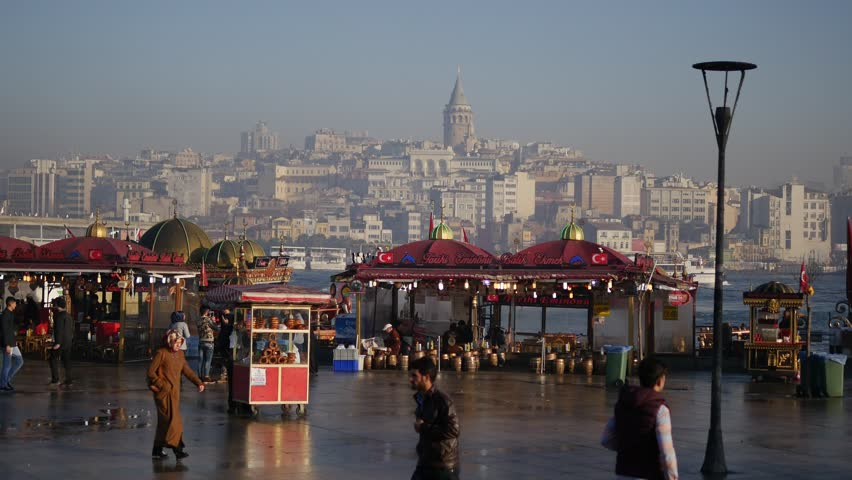 ISTANBUL - DEC 28, 2015: Old city scenery after a rain at waterfront. Eminonu is Istanbul's major hub, a square and a ferry port. The minute after the rain stops, early morning in Istanbul