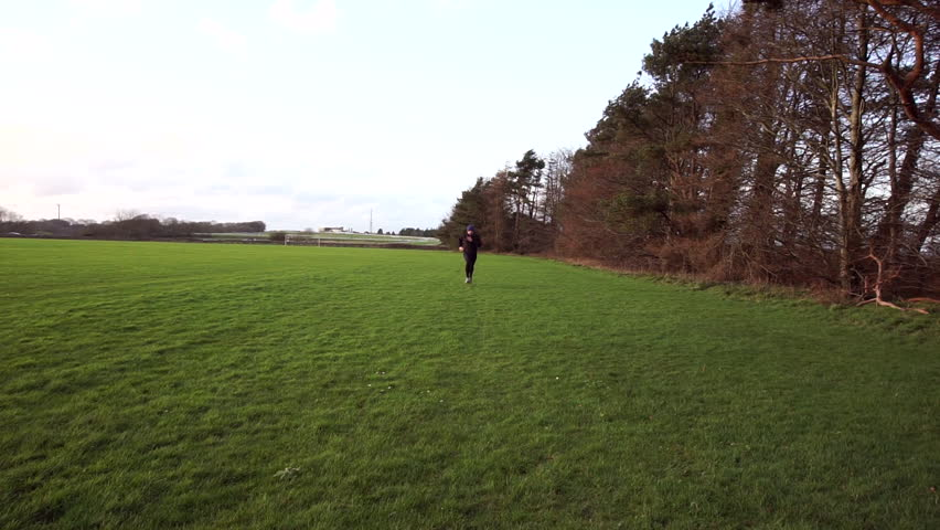 Man running towards and past camera on a winter run in the countryside, wearing warm winter running clothes and hat.