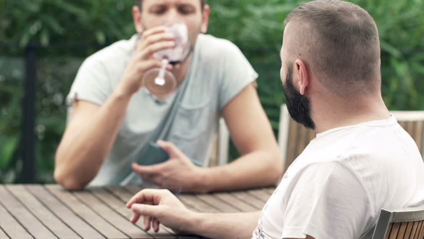 Two male friends talking, smoking cigarette and drinking wine on terrace  - HD stock video clip
