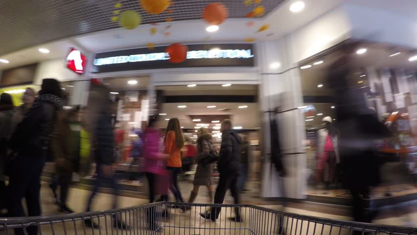KHARKOV, UKRAINE - DEC 5, 2015: Trolley rides through the crowd in shopping mall - 4K stock footage clip