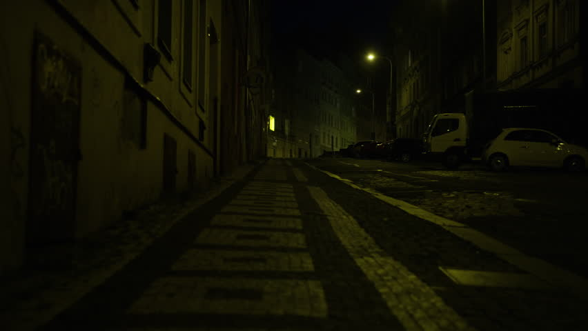 Walking along a street in Prague at night. Czech sign (Vecerka) for 'Convenience Store' at corner. Low angle. 4k.  - 4K stock video clip