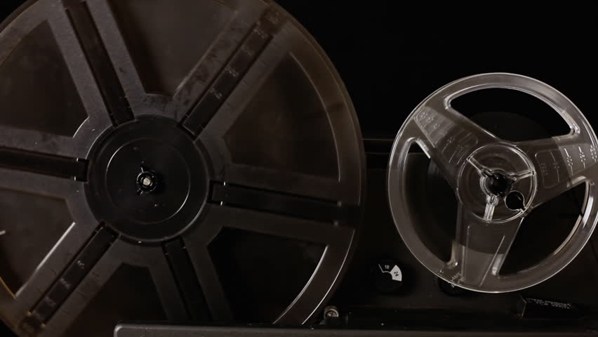 The running film rolls of a vintage Super 8mm projector in action. Detail shot. With diegetic audio.