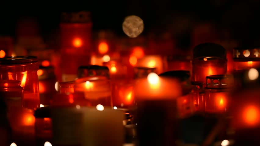 Night shot with burning candles lit in the memory of dead people