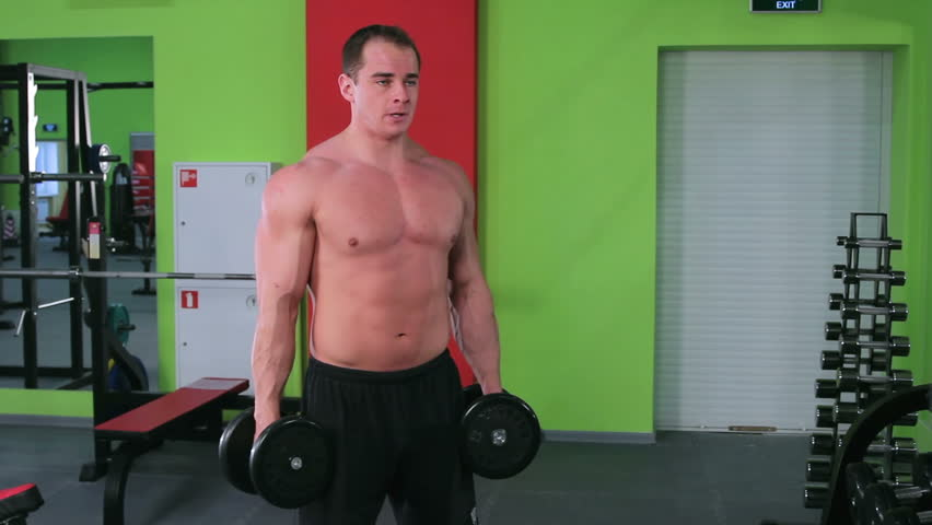 Workout for young bodybuilder. Man doing exercises with dumbbells