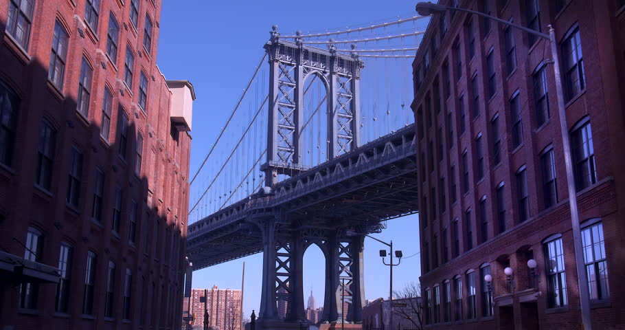 The Iconic Manhattan Bridge Viewed From Dumbo, Brooklyn. Zooming in from between two brick buildings with the Empire State building framed in the bottom of the bridge. (New York, August 2015)