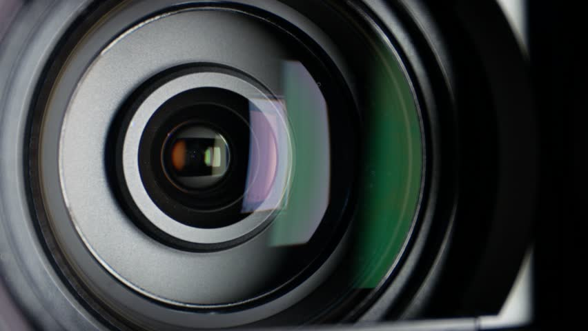 Video camera lens, showing zoom and glare, come to the shadow, close ... Video Camera Lens Reflection