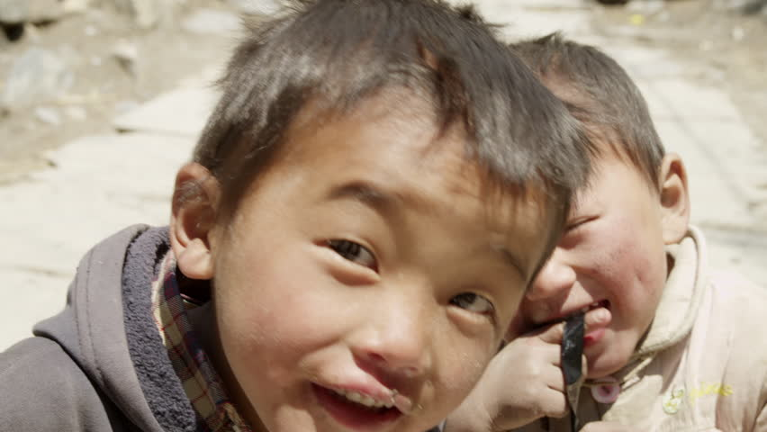 MS TD Shot of child's playing with video tape and smiling / Kabana, Mustang, Nepal - Kabana, Mustang, Nepal, June, 2015 - HD stock footage clip