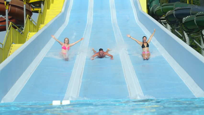 Man Rides By Blue Curvy Aqua Slide In Water Park With