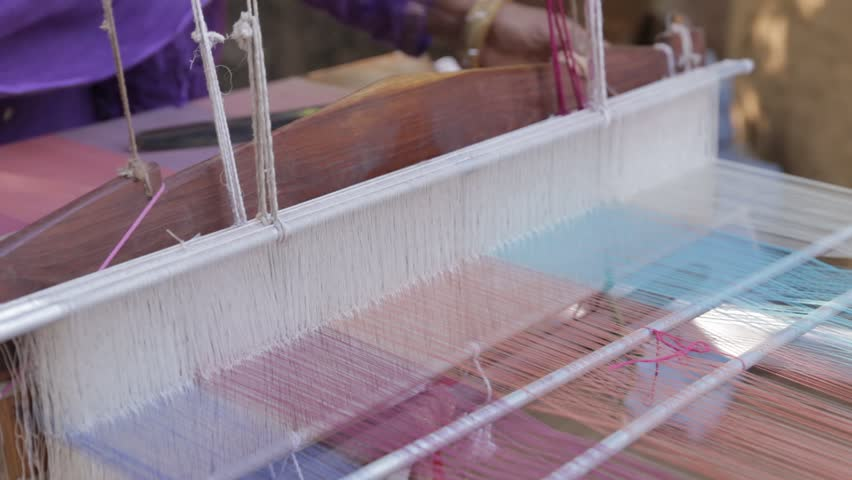 Udaipur, India - December 24, 2015: An old woman making cloth or fabric from threads by hand weaving machine - HD stock video clip