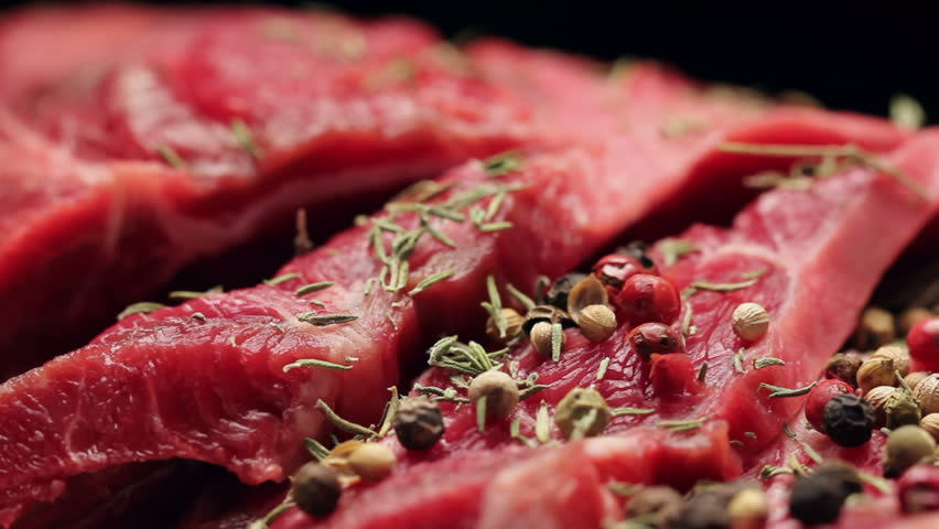 Fresh raw beef meat with peppercorns ready to grill, rotating