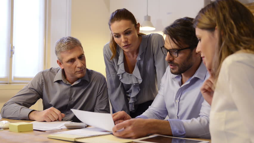 Business team discussing on document and idea at meeting. Businesspeople looking at past history of a company for merger. Meeting in office between creative people, casual business. - HD stock footage clip