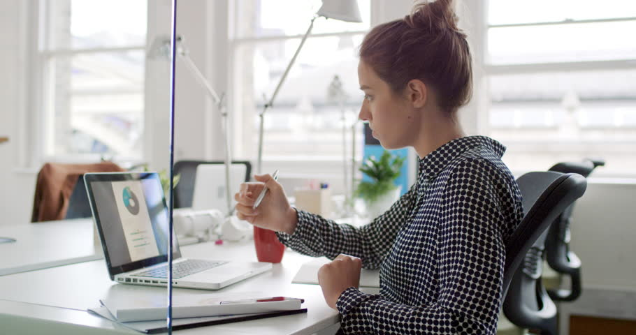 Young business woman working at shared desk in trendy hipster start up office using big data on laptop computer | Shutterstock HD Video #13948937