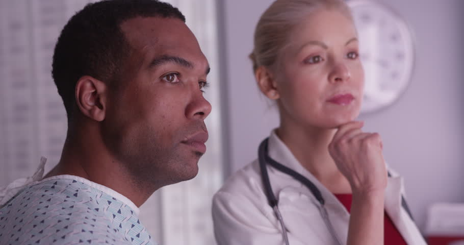 Woman doctor talking about xrays to black patient - 4K stock video clip