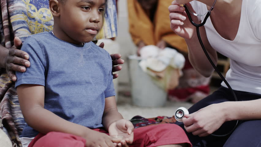 A medical worker from a charity organization lets a little boy use her stethoscope to listen to her heartbeat. In slow motion. | Shutterstock HD Video #13955399