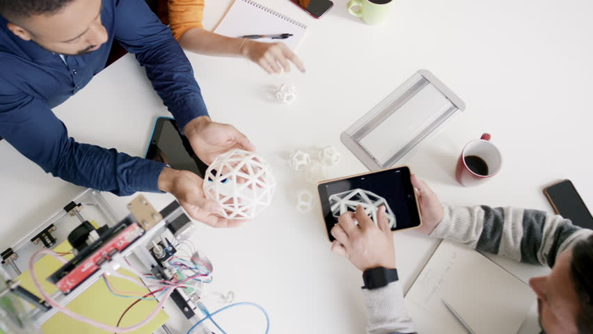 Top view of creative business meeting business man using tablet showing 3d printed shape to engineer discussing new design in modern boardroom | Shutterstock HD Video #13965938