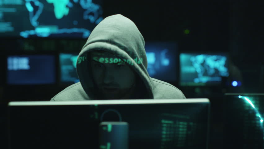 Male hacker working on a computer while green code characters reflect on his face in a dark office room. Shot on RED Cinema Camera in 4K (UHD).