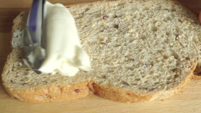 Close up video: spreading creamy butter on a piece of bread