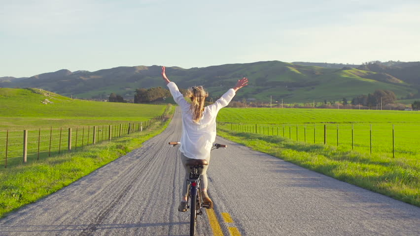 Girl Riding Bike Down Country Road At Sunset With Hands Up In Air