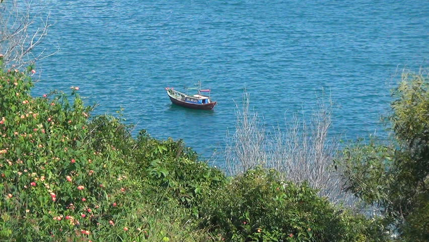 small wooden boat rocking on the waves. Bay is surrounded by greenery. Blue Sea has a slight wave.  - HD stock footage clip