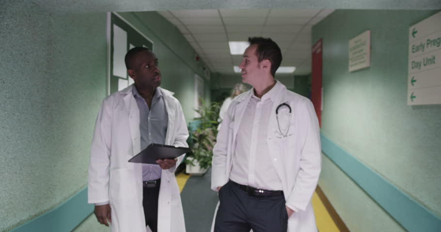 Two Male Doctors Have A Discussion As They Walk Along A ...