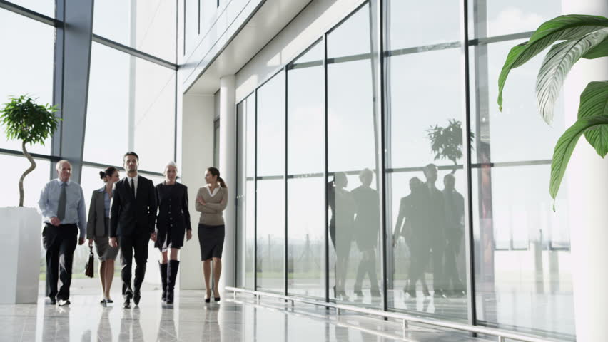 4k / Ultra HD version Portrait of a business team, walking through a light and modern glass fronted office building on a bright day. In slow motion. Shot on RED Epic - 4K stock video clip