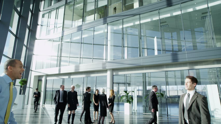 4k / Ultra HD version Two confident and attractive young businessmen meet and shake hands in a busy modern office building. Other workers can be seen walking around the building. Shot on RED Epic - 4K stock video clip