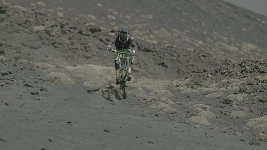 WS MS PAN Mountain biker cycling down mountain / Mount Etna, Province of Catania, Sicily, Italy - 04/06/2013 - HD stock footage clip