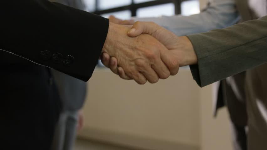 Business people having a handshake in hallway - HD stock video clip