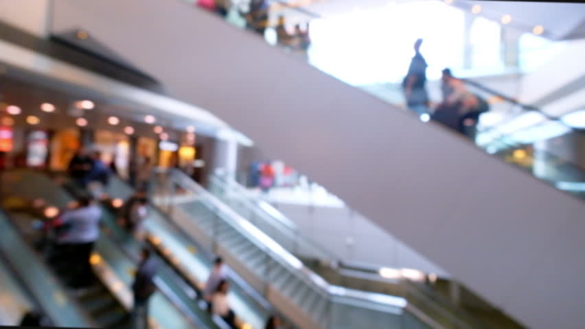 People on moving escalators at modern shopping mall, Hong Kong. Blurred video, unrecognizable people