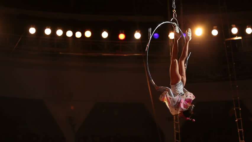 A girl stands in the circus performs acrobatic feats on the hoop.