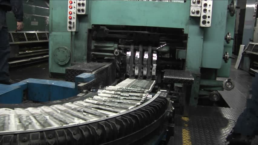 Newspapers move along an assembly line in a factory.