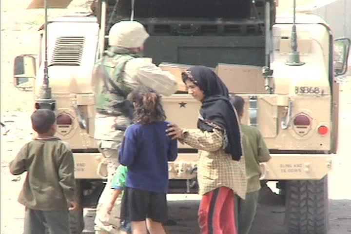 Small children interact with American soldiers along a road in Iraq